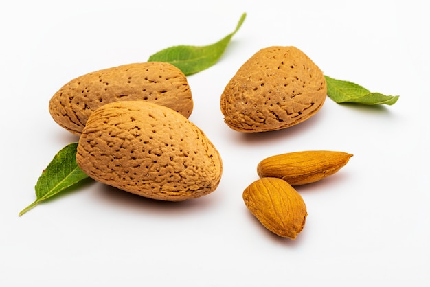 Raw almonds, peeled, with peel, skin (almendrucos) and almond leaves. isolated
