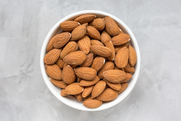 Raw almonds in a porcelain bowl on a gray surface, concept of healthy eating vegan food. close up, selective focus, copy space.