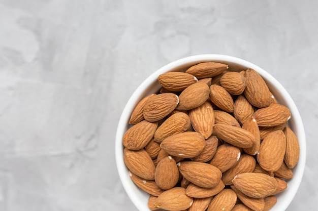 Raw almonds in a porcelain bowl on gray