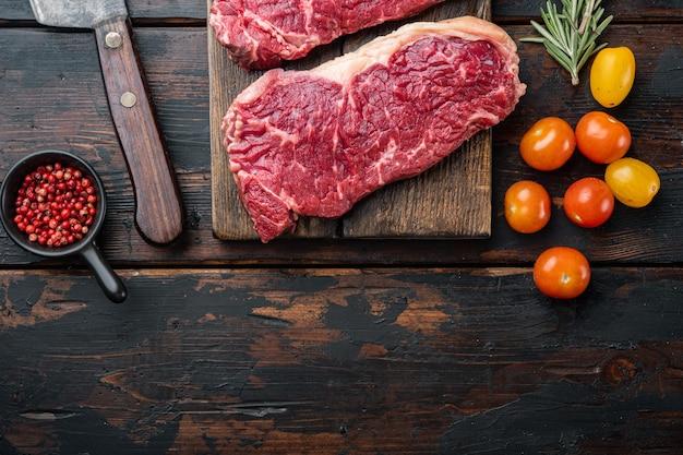 Сырой стейк из говядины посол, на темном деревянном столе, вид сверху