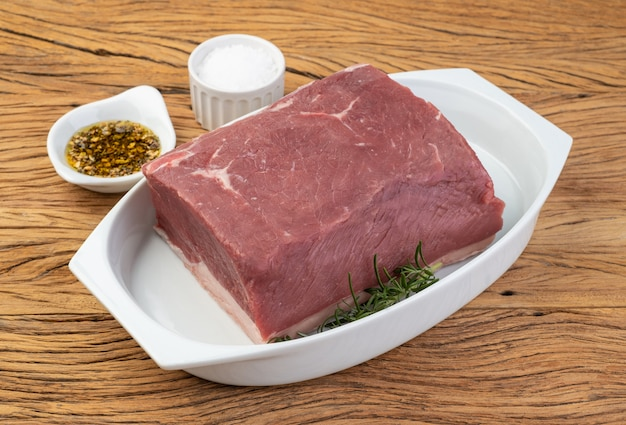 Сырая говядина анчо, типичная аргентинская вырезка, на белой тарелке с приправами.