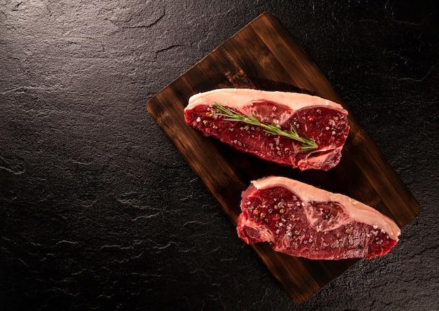 Сырое мясо анчо для приготовления на темной разделочной доске. деревянный фон.