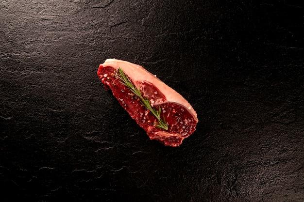 어두운 커팅 보드에 요리하기위한 원시 멸치 고기. 나무 배경입니다.