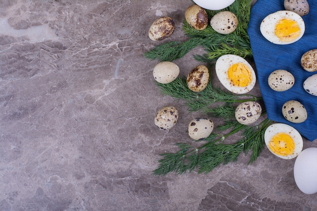 Сырые и вареные яйца с зеленью на синем полотенце