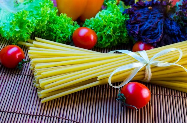 テーブルの上の生と長いパスタと野菜