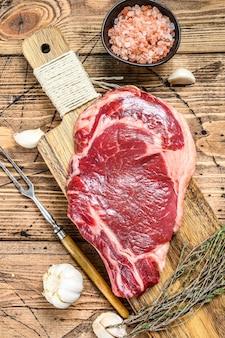 Сырые стейки из говядины ангус, приправленные сверху