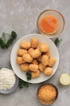 생 아란치니/주먹밥은 동그랗게 빚은 후 빵가루나 판코가루를 바르기 전 단계. 주방에서 요리 준비