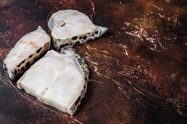 Raw atlantic wolffish fish steak. dark background. top view. copy space.