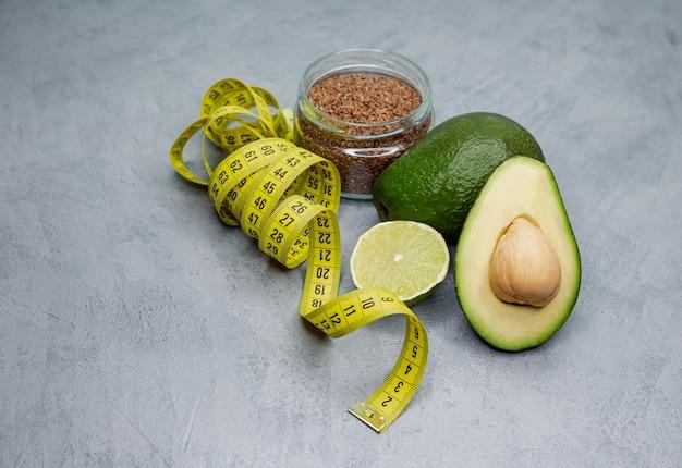 회색 콘크리트 표면에 줄자를 가진 원시 아보카도. 건강한 라이프 스타일, 식사. 적절한 영양. 체중 감량 다이어트. 스포츠 음식. 적합. 해독, 채식주의 자 및 다이어트 개념. 무게를 푸는 방법