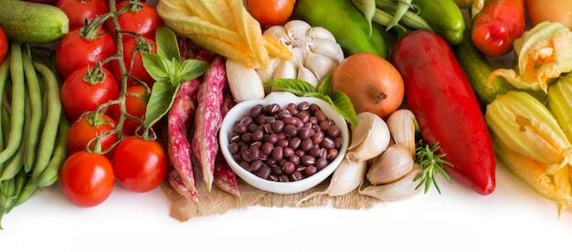 ボウルと新鮮な野菜の生小豆をクローズアップ白で隔離
