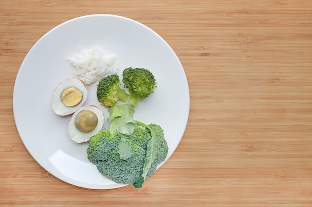 Raw of baby food (broccoli, egg and rice) in white plate on wooden board with copy space.
