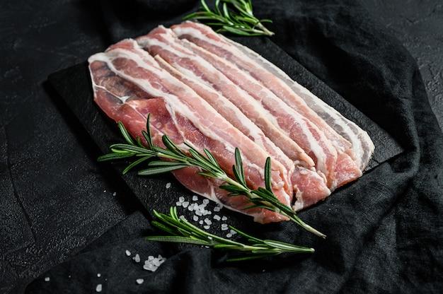 돌도 마 보드에 원시 베이컨입니다. 돼지 고기. 검정색 배경. 평면도 프리미엄 사진