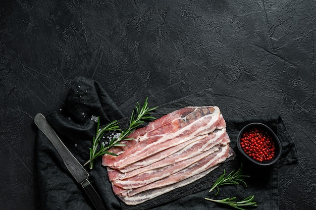 Raw bacon on a stone chopping board.