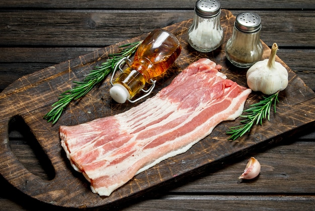 Raw bacon with garlic and aromatic spices. on a wooden background.