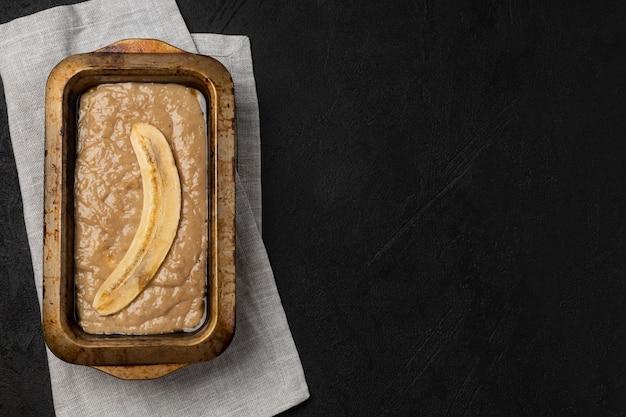 黒の背景に長方形のベーキング皿の生バナナブレッド生地