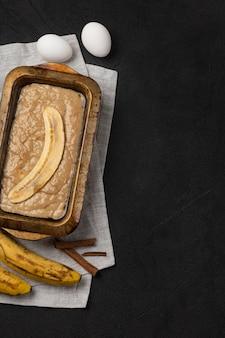 黒の背景に材料と長方形のベーキング皿の生バナナブレッド生地