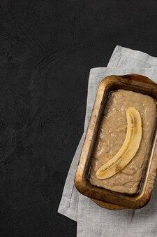 Raw banana bread dough in rectangular baking dish on black background