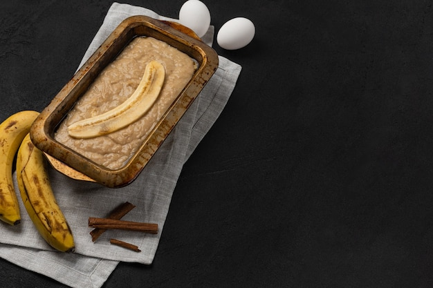Raw banana bread dough in rectangular baking dish with ingredients on black background