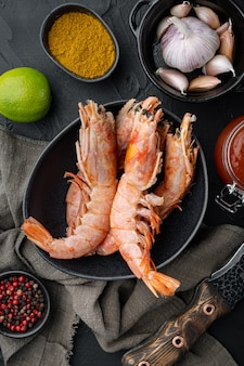Raw barbeque grilling red argentinian prawns ingredients set  in bowl, on black