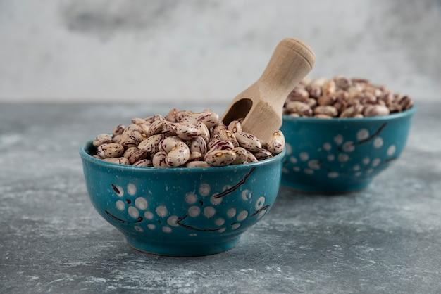 Сырые зерна фасоли выставлены в мисках на мраморной поверхности.