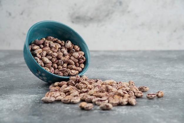 青いボウルに生の豆の粒。