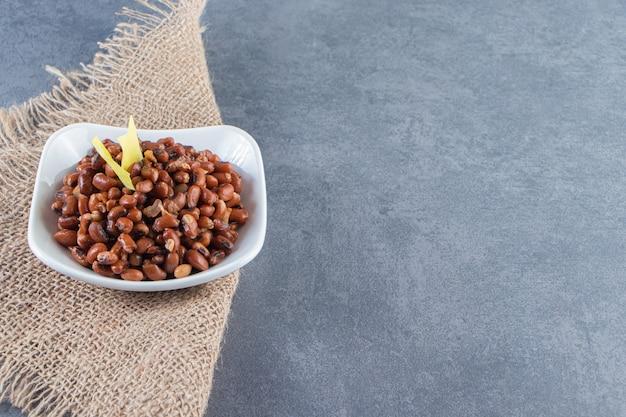 Сырые бобы и листы лазаньи в миске на салфетке из мешковины, на синей поверхности