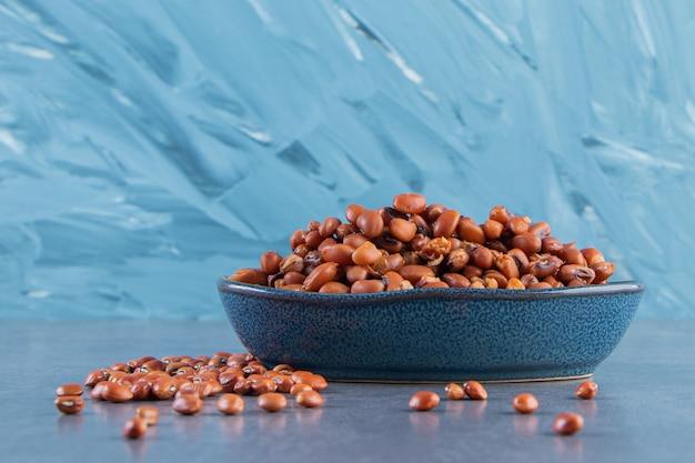 青い背景に、ボウルに生豆。