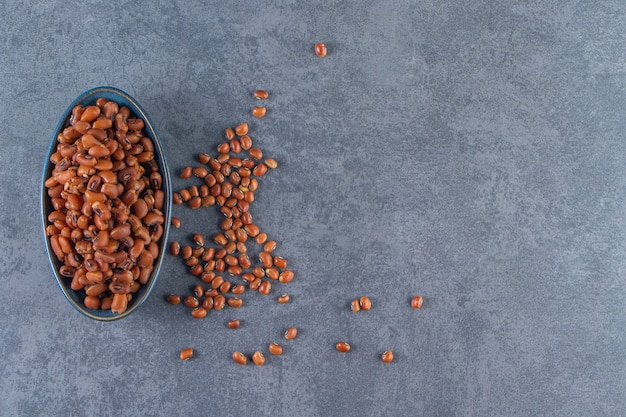 파란색 표면에 그릇에 원시 콩