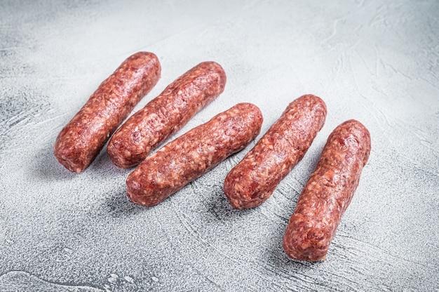 Сырые колбаски кебабы из говядины и баранины на мясном столе. белый фон. вид сверху.