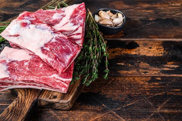 칼으로 정육점 커팅 보드에 원시 쇠고기 송아지 갈비 고기. 어두운 나무 배경입니다. 평면도. 공간을 복사하십시오.
