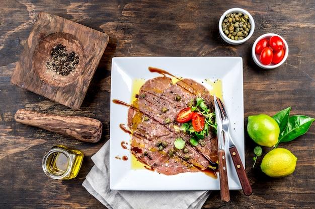 白い皿に生の牛肉のカルパッチョ