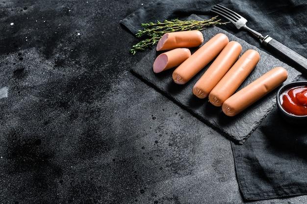 Сырые говяжьи классические колбаски на каменной доске