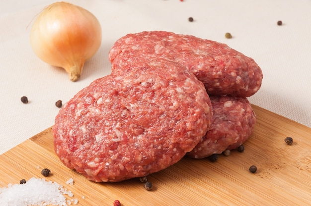 나무 보드에 양파와 원시 쇠고기 커틀릿