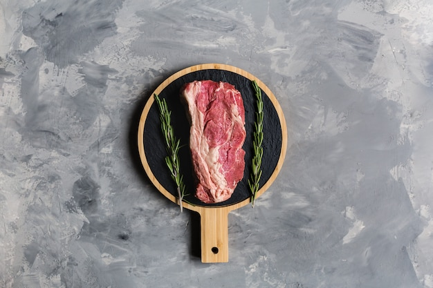 Raw beef on a cutting board with rosemary herb