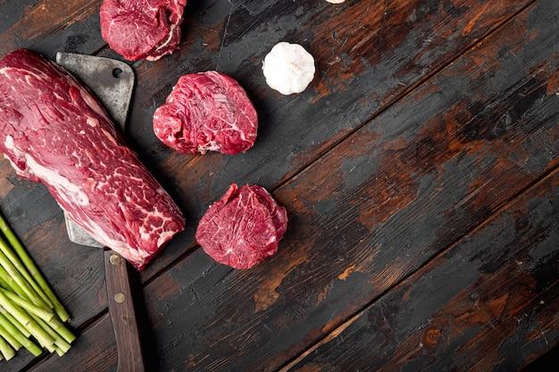 원시 쇠고기 필레 미뇽 스테이크 컷 세트, 오래된 정육점 칼로 오래된 어두운 나무 테이블에