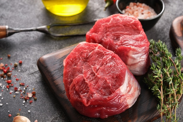 Raw beef filet mignon steak on a wooden board with pepper and salt, black angus marbled meat.