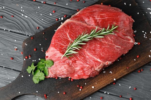 나무 보드에 원시 쇠고기 등심 조각을 닫습니다.