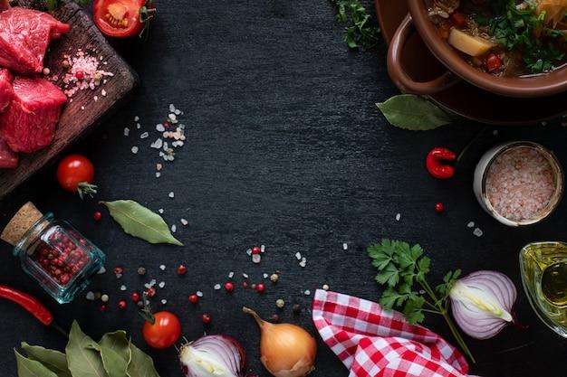 生の牛肉の切り身。チェリートマト、唐辛子、ハーブの木製まな板の上の子牛の切り身。スープやボルシチの材料。コピースペース。上面図。