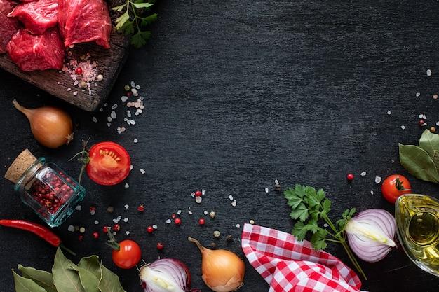 Сырое филе говядины готово к приготовлению на гриле. филе телятины на деревянной разделочной доске с помидорами черри, острым перцем и зеленью. ингредиенты для супа или борща. копировать пространство. вид сверху.