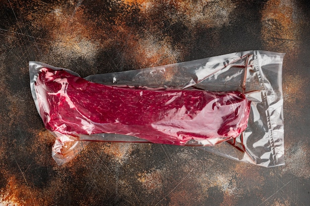 Raw beef fillet steaks mignon whole cut in plastic airtight pack set, on old dark rustic background, top view flat lay