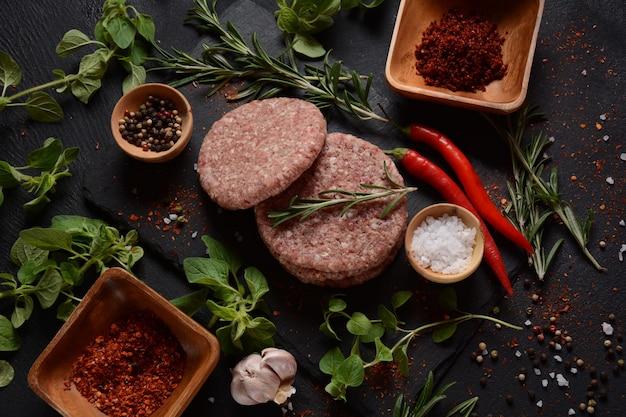 Котлеты для гамбургеров из сырой говядины с травами и специями. сырые котлеты бургер на бетонном фоне