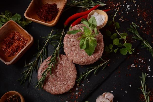 허브와 향신료를 곁들인 생 쇠고기 햄버거 패티. 콘크리트 배경에 생 버거 커틀릿