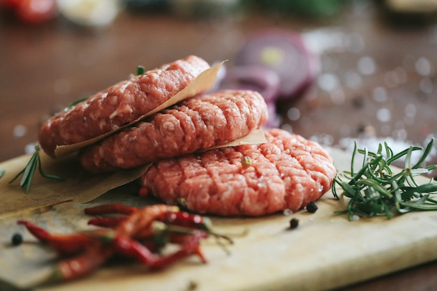 Raw beef hamburger patties with herbs and spices