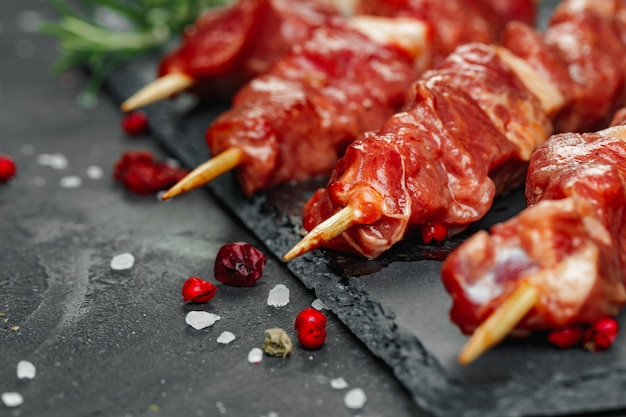 Raw beef kebab with herbs on a dark board, close up