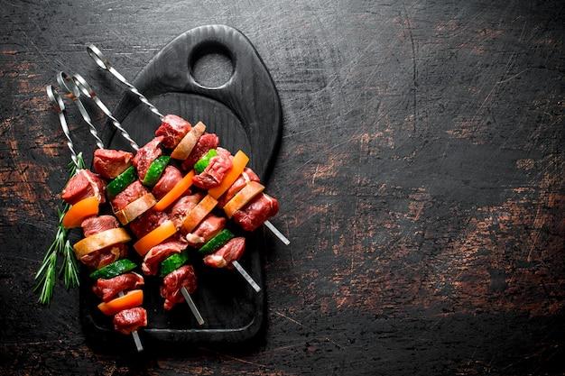 야채와 허브 커팅 보드에 원시 쇠고기 케밥. 소박한 표면에