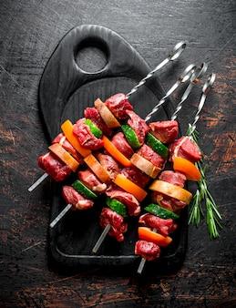 まな板の上に野菜とハーブを添えた生の牛肉のケバブ。素朴な表面に