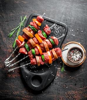 生の牛肉のケバブと野菜とスパイスのボウル。暗い素朴な表面に