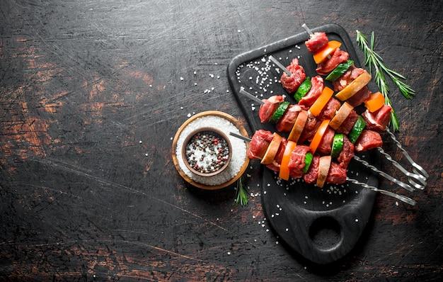 Сырой шашлык из говядины с овощами и специями в миске. на темной деревенской поверхности