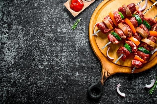 ソース、ローズマリー、タマネギのスライスとまな板の上に野菜と生の牛肉のケバブ。素朴に