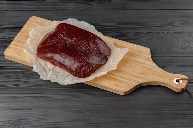 テーブルの上の木の板の生の牛レバー
